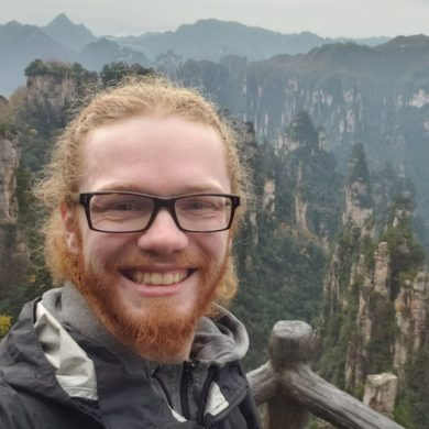 Jake Pfund at a scenic lookout in Zhangjiajie National Forest Park in Hunan, China, with a dramatic rocky landscape behind him