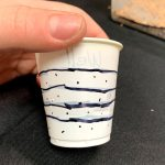 Small plastic cup with holes poked through the sides and lines drawn on it to represent a groundwater well